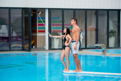 Girl in a black sexy bikini posing near swimming pool taking selfie photo with selfie stick and guy standing behind her. Smiling girl in a black sexy bikini Stock Photos
