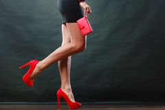 Girl in black short dress red spiked shoes holds handbag. Celebration disco and evening fashion concept. Woman in black short dress red spiked shoes holding Royalty Free Stock Photography