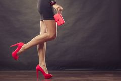 Girl in black short dress red spiked shoes holds handbag. Celebration disco and evening fashion concept. Woman in black short dress red spiked shoes holding Royalty Free Stock Image