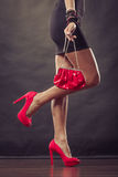 Girl in black short dress red spiked shoes holds handbag Royalty Free Stock Image