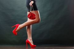 Girl in black short dress red spiked shoes holds handbag Royalty Free Stock Photo