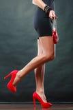 Girl in black short dress red spiked shoes holds handbag Stock Image