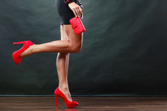 Girl in black short dress red spiked shoes holds handbag Royalty Free Stock Photography