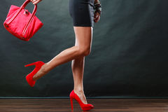 Girl in black short dress red spiked shoes holds handbag Royalty Free Stock Photos
