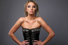 Girl in a black and silver corset. On gray background Stock Photography