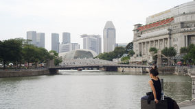 Girl in Black Sitting by Singapore River Stock Images