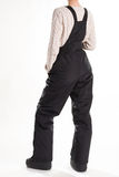 Girl in a black ski jumpsuit and moon boots. Royalty Free Stock Photography