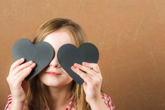 Girl and black slate heart. The girl builds a physiognomy, grimaces and a heart for an inscription. Valentine`s Day concept, close stock photos
