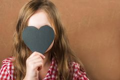 Girl and black slate heart. The girl builds a physiognomy, grimaces and a heart for an inscription. Valentine`s Day concept, close. Up and copy space royalty free stock images