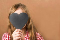 Girl and black slate heart. The girl builds a physiognomy, grimaces and a heart for an inscription. Valentine`s Day concept, close stock photo