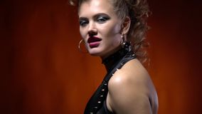A girl in black spiky rock clothes, showing a peace sign and her tongue. Blonde woman in rock clothes, with makeup and amazing hairstyle, showing her tongue and stock footage