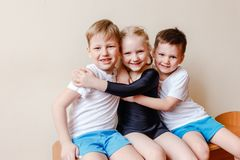 Girl in a black sports swimsuit, boys in white t-shirts. Kids pre-school children in sports uniform, girl in a black sports swimsuit, boys in white t-shirts royalty free stock image