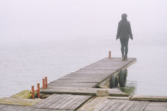 Girl in black standing on dock on misty autumn day waiting Royalty Free Stock Image