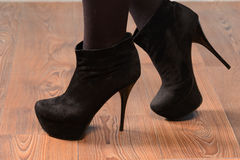 Girl in black suede boots with high heels Royalty Free Stock Image