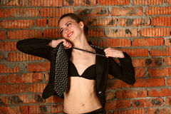 Girl in black suit takes off necktie. Royalty Free Stock Images