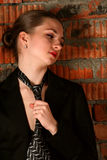 Girl in black suit tuck her necktie. Stock Images