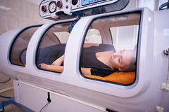 A girl in a black T-shirt lies in a hyperbaric chamber, oxygen therapy royalty free stock photo