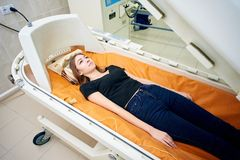 A girl in a black T-shirt lies in a hyperbaric chamber, oxygen therapy stock image