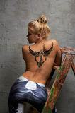 Girl with black temporary tattoo painted with paints for body art. Blonde half naked girl with black temporary tattoo painted with paints for body art Royalty Free Stock Photos