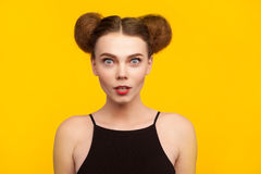 Girl in black top staring at camera. Brunette young woman shocked wearing black top staring at camera with open mouth standing against yellow background Royalty Free Stock Image