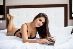 girl in black underwear with laptop in bed at home Stock Photo
