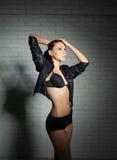 Girl in black underwear over white brick wall. Studio shot Royalty Free Stock Photos