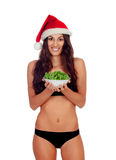 Girl in black underwear and a Santa hat and a salad Stock Photo