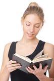 Girl in black vest reads book Stock Photo