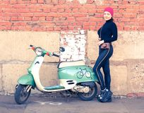 The girl in black at the vintage green scooter wit. H vintage the camera. Hipster Royalty Free Stock Photography