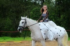 Girl in black and white dress on a white horse. Royalty Free Stock Photo