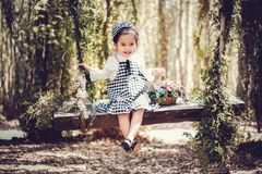 Girl in Black and White Overall Skirt Holding Basket With Petaled Flowers royalty free stock images