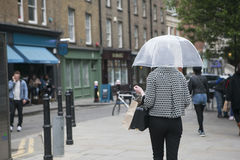 A girl in a black and white plaid fashion jacket under a transparent umbrella against the backdrop of London Stock Images