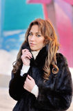 Girl in a black winter coat on a bright background Stock Image