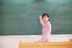 Girl before blackboard Royalty Free Stock Photography