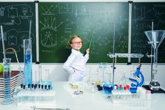 Girl at blackboard. Clever schoolgirl stands by a chalkboard on a chemistry lesson. Educational concept stock photos