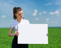 Girl with blank billboard on green field Stock Image