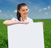 Girl with blank billboard on green field Royalty Free Stock Photography