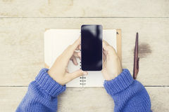 Girl with blank black cell phone and opened diary on wooden table royalty free stock images