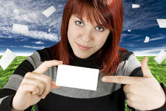 Girl and Blank Card in Sky. Cute redhead girl pointing at a blank business or greeting card royalty free stock images
