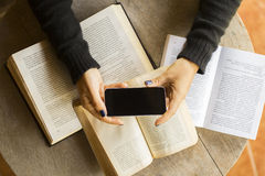 Girl with blank cell phone and books Royalty Free Stock Photos