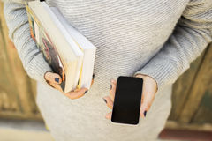 Girl with blank cell phone and books Stock Photo