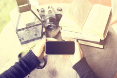 Girl with blank cell phone, books and old camera Royalty Free Stock Image
