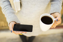 Girl with blank cell phone, cup of coffee and books Royalty Free Stock Images