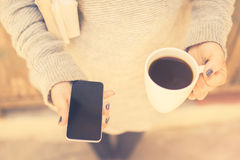 Girl with blank cell phone, cup of coffee and books, vintage pho Stock Images