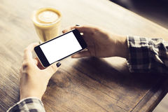 Girl with blank cell phone and cup of coffee Royalty Free Stock Photography
