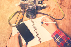 Girl with blank cell phone, diary and old camera Royalty Free Stock Photos