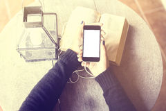 Girl with blank cell phone, headphones and a book Royalty Free Stock Photos