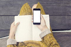 Girl with blank cell phone screen and blank diary on wooden bench, mock up stock image