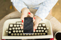 Girl with blank cell phone and typewriter Stock Photo