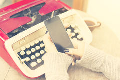 Girl with blank cell phone and typewriter Royalty Free Stock Image